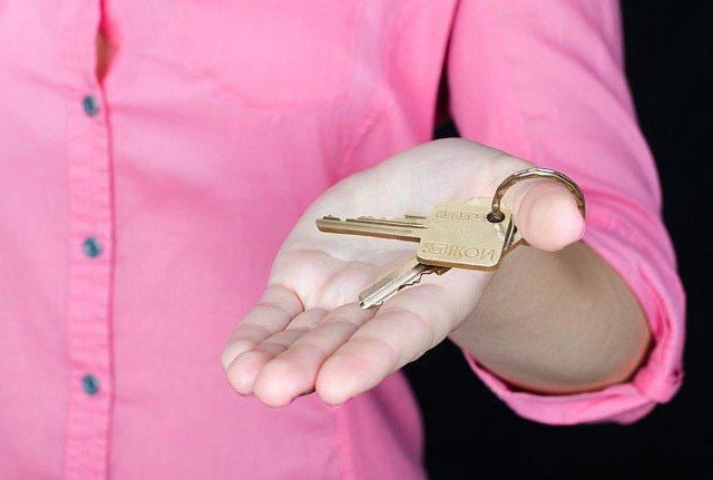 agent nieruchomości wręczający klucz do mieszkania